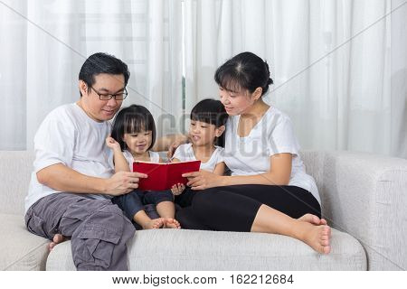 Happy Asian Chinese Family Reading Book On The Couch