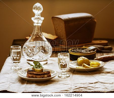 Sprat sandwiches of rye bread with vodka and salted cucumbers in a rustic wooden setting