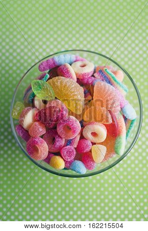 Glass bowl filled with brightly colored sweets (fruity jelly sweets).