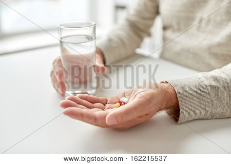 age, medicine, healthcare and people concept - close up of senior man hands with pills and water glass at home