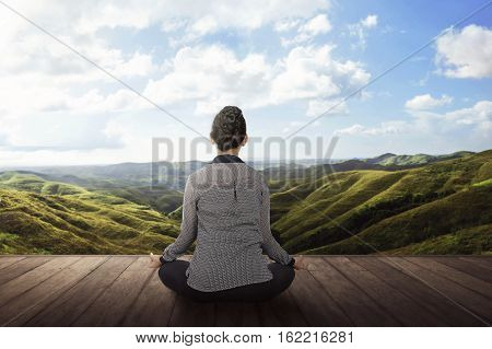 Rear View Of Asian Woman Doing Meditation On The Wooden Floo