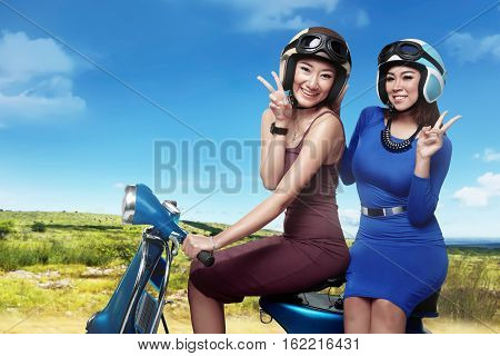 Happy Two Asian Woman Having Fun Riding The Scoote