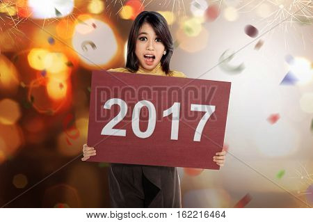 Happy asian woman holding number 2017 on the red board against blurred light
