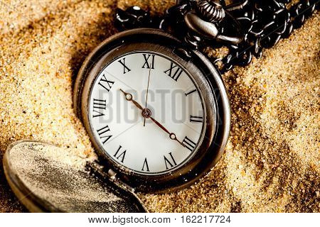 deadline concept pocket watch in sand background close up.