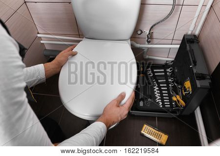 Plumber fixing toilet seat lid
