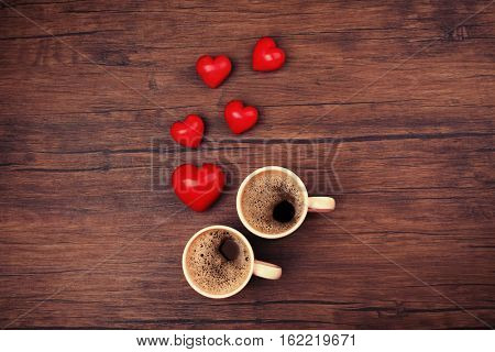 Two cups of coffee with red hearts on wooden background, top view