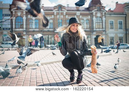 Young beautiful woman is feeding pigeons with bread crumbs in the town square on a sunny autumn day