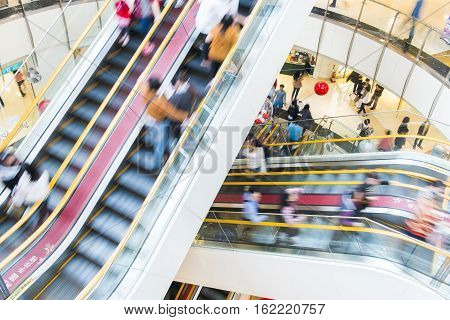 People in motion in escalators at the modern shopping mall