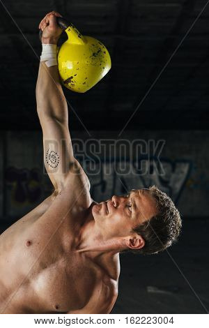 Front view of inclined man holding dumbbell up on blurred background. Vertical indoor shot