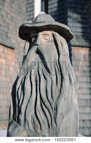 Carved wooden mountain spirit. Carved wooden statue old grandfather with a hat in Sumava Czech Republic. Old wooden sculpture