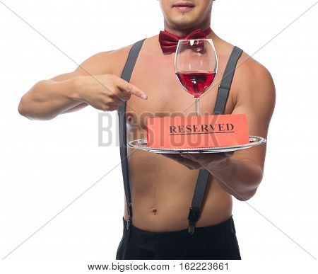 handsome waiter points to a glass of red wine on a tray