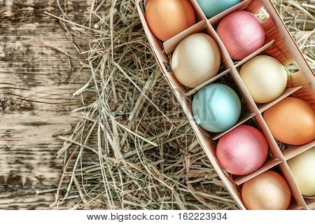 Box with colorful Easter eggs on wooden table