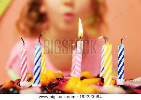 Close up view of birthday cake with one burning candle