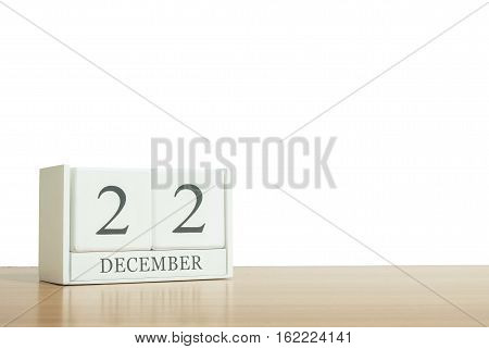 Closeup surface white wooden calendar with black 22 december word on blurred brown wood desk isolated on white background with copy space selective focus at the calendar