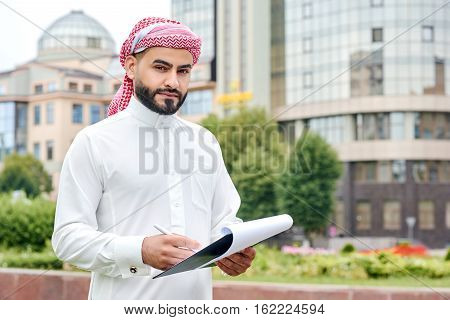 Arabic Businessman With Blueprints Outdoors