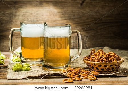 Two glasses of beer froth with hop and pretzels on wooden table