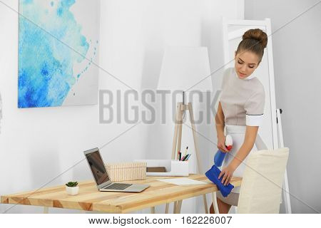 Hotel service concept. Chambermaid cleaning table from dust
