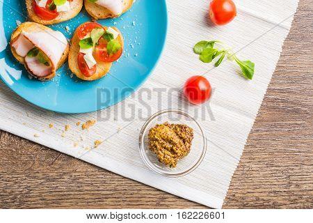 Traditional Italian antipasti bruschetta with tomato, cheese and bacon. Flat lay.