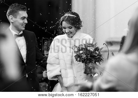 Bride Looks Shying Under The Rain Of Rice After The Ceremony