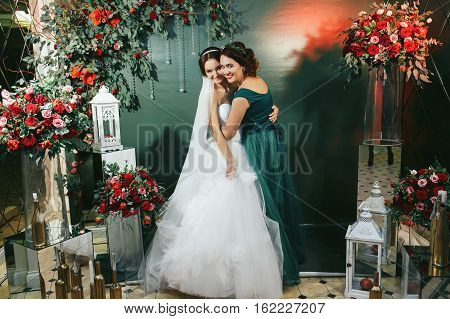 Bride and bridesmaid hug among the red bouquets