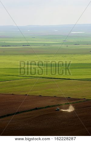 Aerial view of a tractor working a large farming area in Valladolid Spain