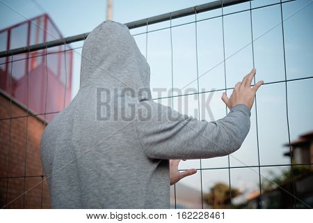 Hooded Man Prisoner With Hand On A Metal Mesh
