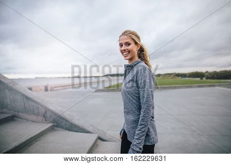 Fitness Woman Standing Outdoors And Smiling