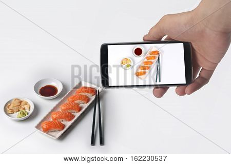 Use phone to take Photo the salmon sushisushi nigiri with salmonor share to social network.