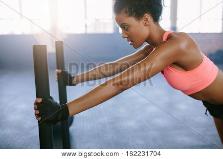 Side view shot of strong young woman pushing the sled at gym. African woman doing intense physical workout in gym.