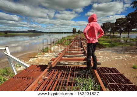 A female looks out over the floodwaters from the buckled train tracks at Crowther Hilltops Region Country NSW.
