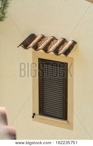 Window with brown closed shutters. Rain protection from roof tiles in a yellow painted house wall.