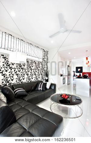 Close up of a black sofa with pillows near round table like a drum. The wall have better look with vine's art pasting next to the flashing white lamp. The hallway starts from living room with a fan