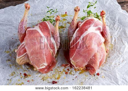 Ready to cook raw seasoned partridges with bacon on crumpled paper