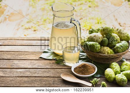 Noni fruit  and noni juice with noni powder and wooden spoon on wooden table.Fruit for health and herb for health.
