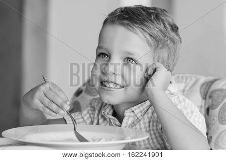 happy little boy eating soup in the cafe ( black and white )