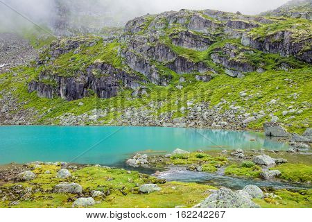 Small mountain lake with turquoise glacial water in Jostedalsbreen National Park Norway