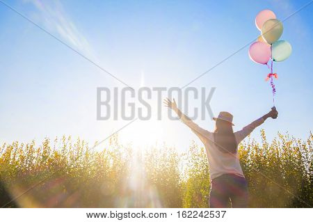 Girl running on the field of yellow flowerwith balloons at sunset. Happy woman on nature concept about carefree airiness and relax vintage effect.