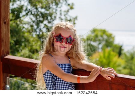 Cute little girl is having fun on a terrace near the sea beach