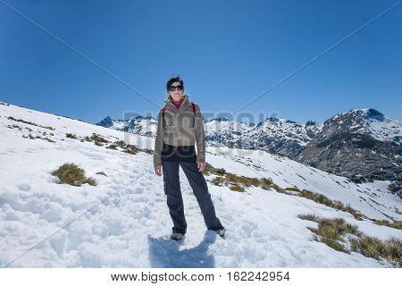 brunette sport active woman with green jacket black trousers and sunglasses posing looking in snow with blue sky in Gredos mountain Avila Spain Europe
