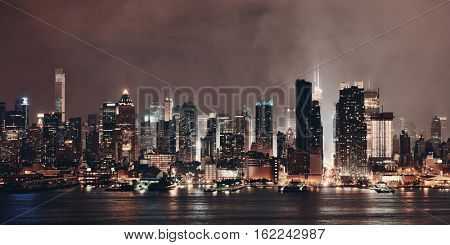 Manhattan panorama midtown skyscrapers and New York City skyline at night with fog