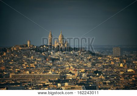 Paris city skyline rooftop view and Sacre Coeur cathedral at sunset, France.