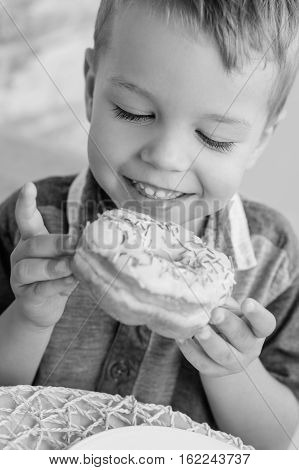 happy little boy eats the sweet donut ( black and white )
