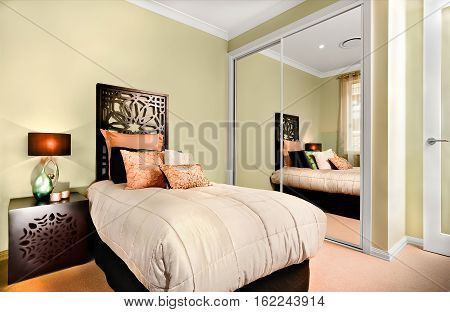 Single bed and the small table are made of wooden with carve. There is a table lamp on a cupboard and some glossy look fancy items on it. A huge mattress and few pillows on it. The mirror attached to green wall.