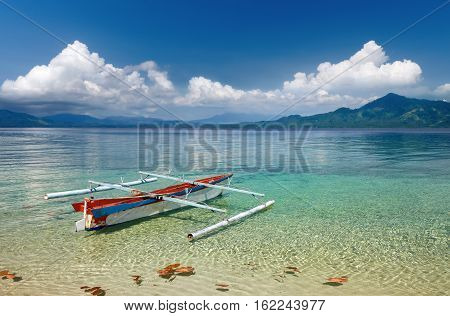 Beautiful summer landscape with an Indonesian boat on the beach on a background of the tropical island of Sulawesi. Indonesia