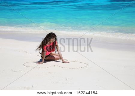 Enjoyment. Beautiful Carefree Brunette Girl Drawing Heart On Sand In Bikini Relaxing On Exotic Beach