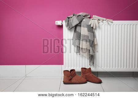 Warm clothes drying on heating radiator with shoes beside on the floor