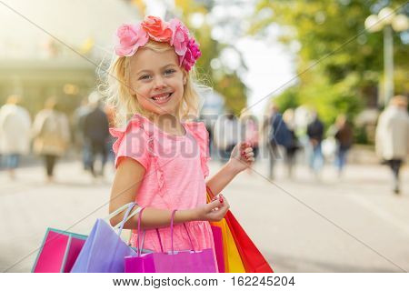 little fashionista holding shopping bags and  smiling