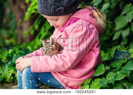 Portrait of adorable child with kitten outdoors