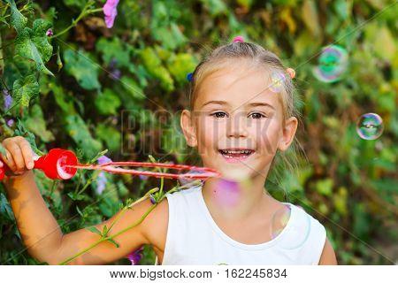 Summer portrait of happy little child with soap bubbles