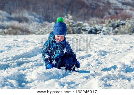 Cheeked happy toddler child touches the snow mountains in the background